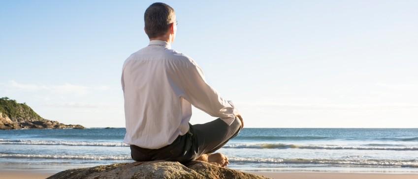 Businessman meditating on a beach